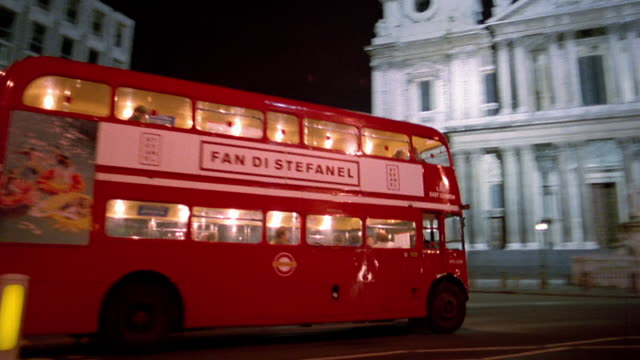 Medium shot pan double decker bus driving past St. Paul's Cathedral at night / London, England