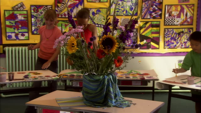 Medium shot pan elementary school children painting flower arrangement in art class/ London