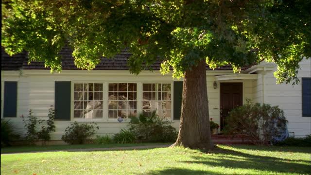 medium shot pan establishing shot suburban house w/tree in front yard - in front of stock videos & royalty-free footage