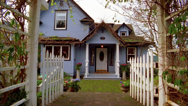 medium shot pan ext lavender house and white picket fence / bainbridge island, washington - picket fence stock videos and b-roll footage