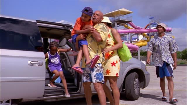 medium shot pan family exiting minivan / man opening trunk / family unloading water toys - water slide stock videos & royalty-free footage