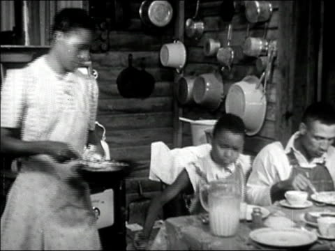 vídeos de stock e filmes b-roll de 1942 medium shot pan family sitting down to meal in rustic kitchen/ macon, georgia/ audio - 1942