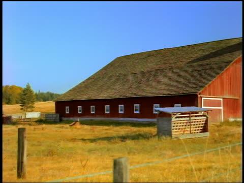 Medium shot pan farm building with silos in grassy field / Olympic Peninsula, Washington