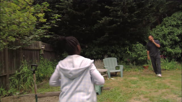 medium shot pan father playing tossing football with son and daughter in backyard - fence stock videos & royalty-free footage