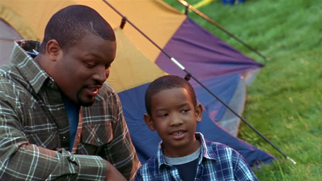 vídeos y material grabado en eventos de stock de medium shot pan father talking to son in front of tent / smiling at cam / illinois - camping