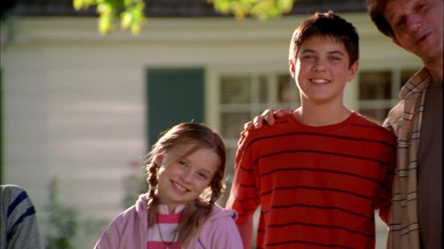 vidéos et rushes de medium shot pan father w/two boys and girl + dog posing in yard - balançoire pneu