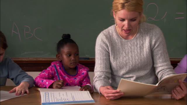 medium shot pan female elementary school students listening to teacher read / writing - pacific islander teacher stock videos & royalty-free footage