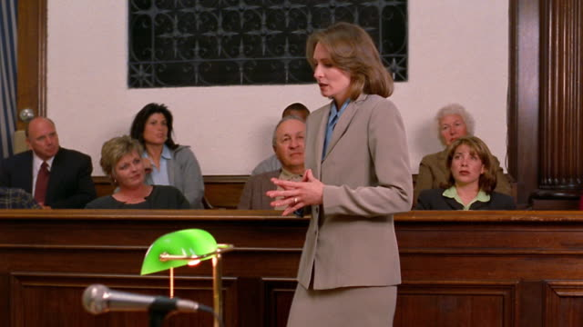 Medium shot pan female lawyer talking to jury / opposing lawyer in foreground