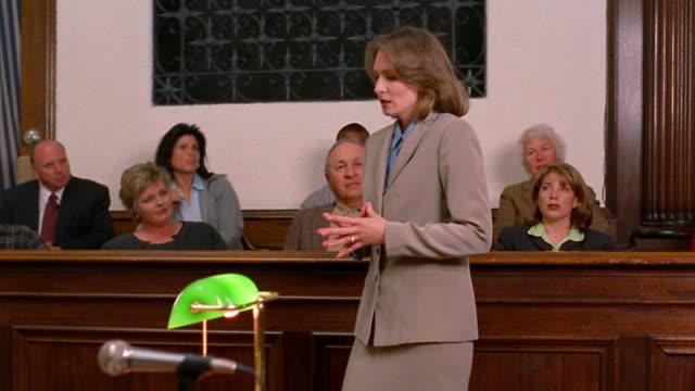 medium shot pan female lawyer talking to jury / opposing lawyer in foreground - 弁護士点の映像素材/bロール