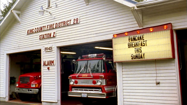 """medium shot pan fire station w/parked fire trucks and flashing sign """"pancake breakfast this sunday"""" - fire station stock videos & royalty-free footage"""