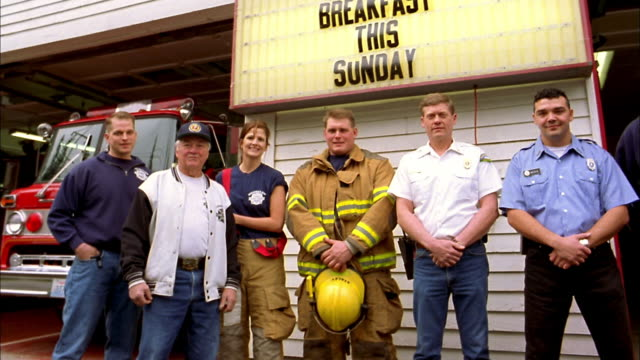 medium shot pan firefighters standing in front of fire station and smiling at cam w/fire trucks+ sign in background - fire station stock videos & royalty-free footage