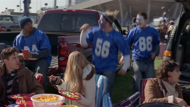 medium shot pan football fans with painted faces running around at tailgate party/ connecticut - アメフトのユニフォーム点の映像素材/bロール