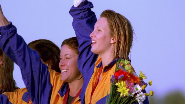 vidéos et rushes de medium shot pan four female swimmers celebrating with medals on victory stand - award