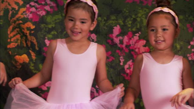 medium shot pan four girls wearing tutus posing on stage - pacific islander background stock videos & royalty-free footage