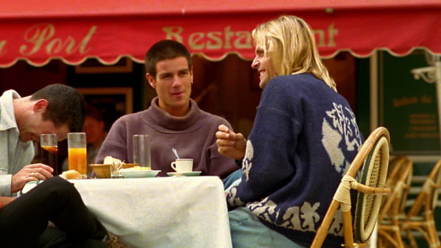 stockvideo's en b-roll-footage met medium shot pan four young adults sitting eating, drinking and talking at outdoor cafe / cannes, france - franse cultuur