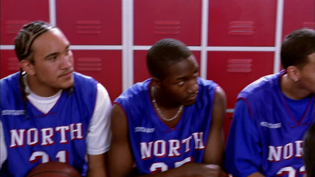 vidéos et rushes de medium shot pan from basketball players to coach explaining plays in locker room - personne sportive
