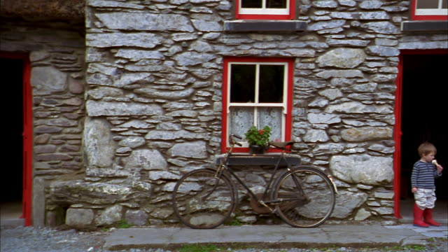 medium shot pan from bicycle against stone building to boy eating ice cream cone in doorway / cork - county cork stock videos & royalty-free footage