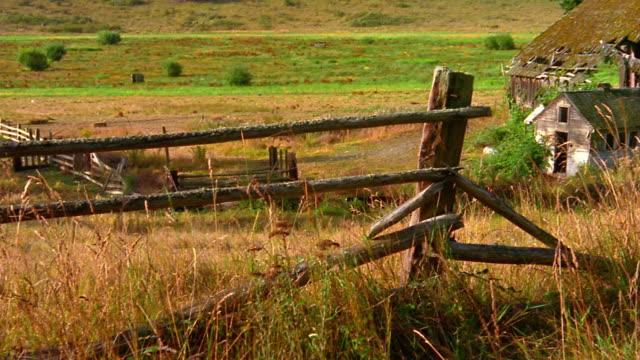 Medium shot pan from broken wooden fence to abandoned barn with tall grass / Olympic Peninsula, Washington