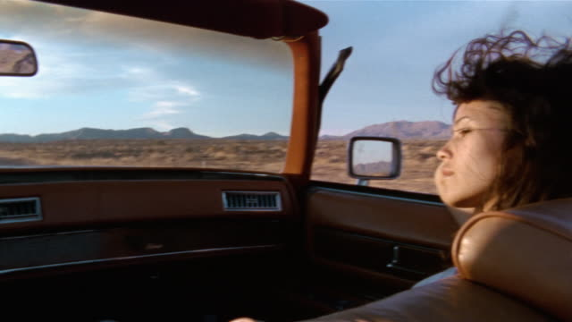 Medium shot pan from brunette woman riding in car to blonde woman driving convertible through desert / Baja, Mexico