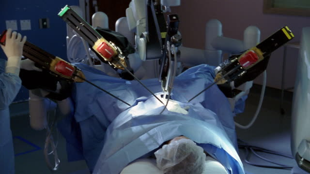 Medium shot pan from monitor to surgeon sitting at console to woman positioning arms during robotic surgery