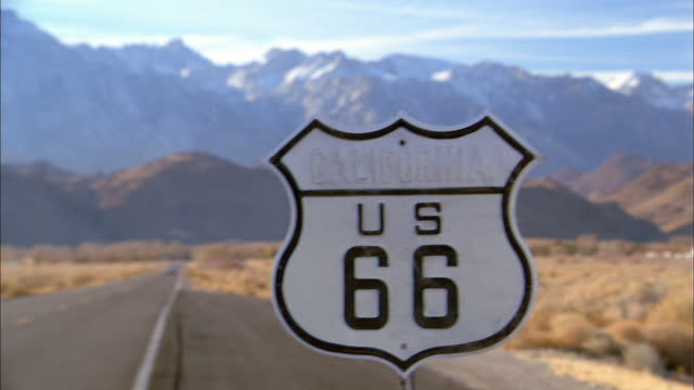 vidéos et rushes de medium shot pan from route 66 road sign to convertible driving to side of road - route 66