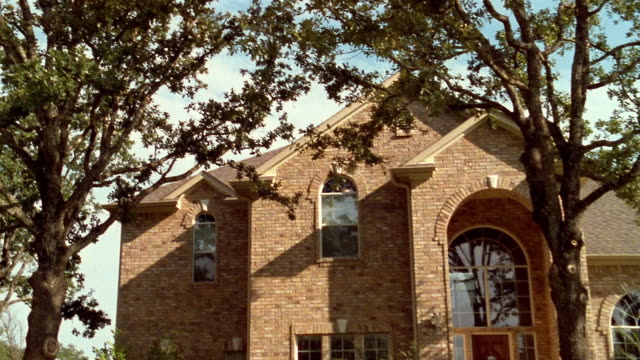 medium shot pan from tree to exterior of house - texas stock videos & royalty-free footage