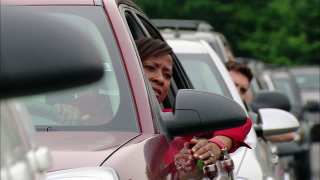 vídeos y material grabado en eventos de stock de medium shot pan frustrated drivers sticking heads out car windows during traffic jam - vídeo de alta definición