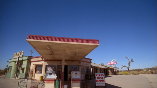 vidéos et rushes de medium shot pan gas station complex with motel to the right+ diner to the left - station service