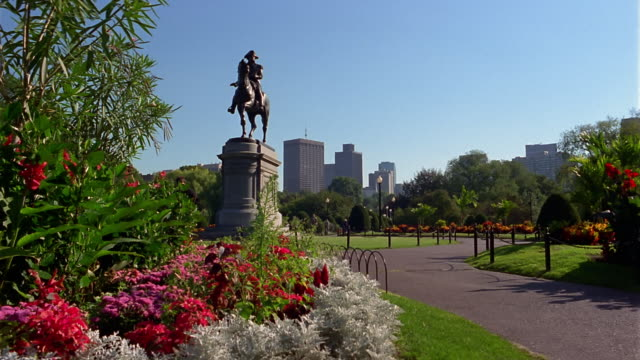 Medium shot pan George Washington statue in Boston Public Garden with skyscrapers in background / Boston