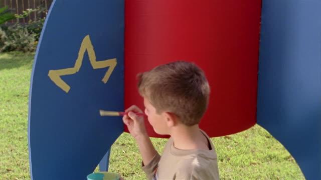 medium shot pan girl and boy building large model rocket in backyard - hammer stock-videos und b-roll-filmmaterial