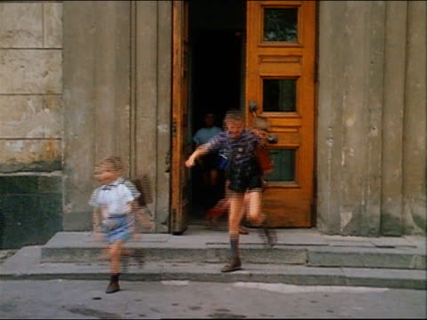 vídeos de stock e filmes b-roll de 1967 medium shot pan girls and boys running out of school / russia - rússia