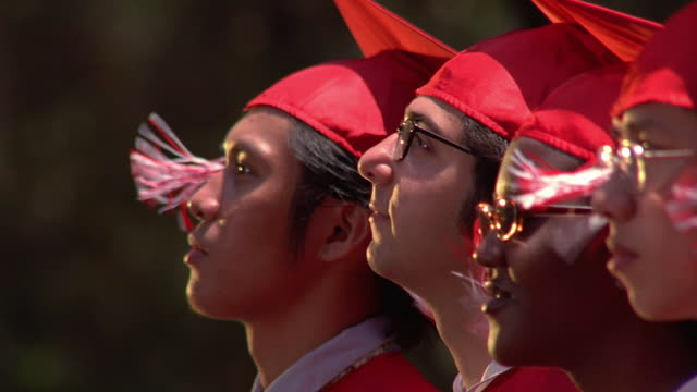 Medium shot pan group of high school seniors in caps and gowns at graduation / Los Angeles, California