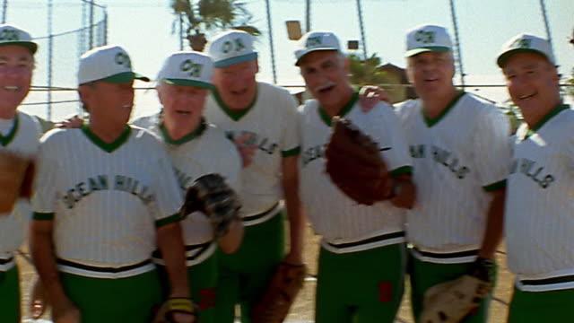 vídeos y material grabado en eventos de stock de medium shot pan group of senior men in baseball uniforms standing on field talking - sófbol