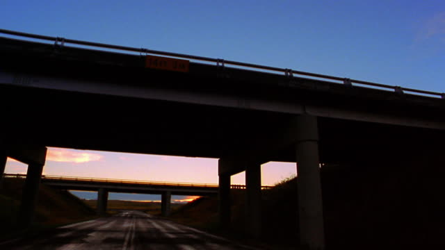 Medium shot pan highway overpasses / tractor trailer driving across overpass / Nevada