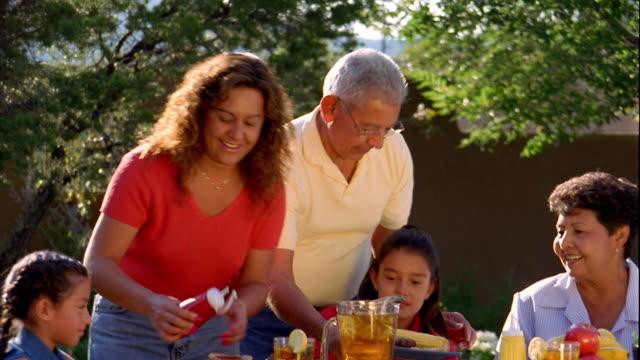 medium shot pan hispanic woman and older man serving food to family sitting around table outdoors / santa fe - アイスティー点の映像素材/bロール