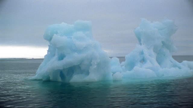 medium shot pan iceberg floating in water / arctic - nick berg stock videos & royalty-free footage