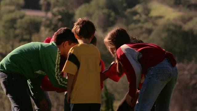 Medium shot pan kids bending down in huddle / forming line / playing football