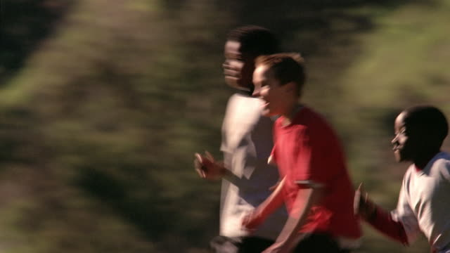 Medium shot pan kids in a line running towards other team / kids chasing each other