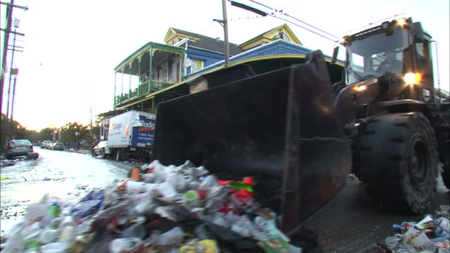medium shot pan left - garbage truck sweeping trash down the street / new orleans louisiana - vehicle scoop stock videos and b-roll footage