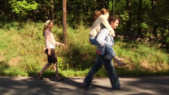 medium shot pan man and two women walking along side of country road / woman hopping on man's back for piggyback ride - 男性と複数の女性点の映像素材/bロール