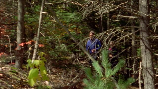 Medium shot pan man and woman trail running through woods / Bradbury Mountain, Maine