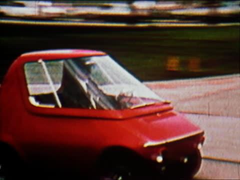 vídeos de stock e filmes b-roll de 1970 medium shot pan man driving tiny red fuel-efficient car - pequeno