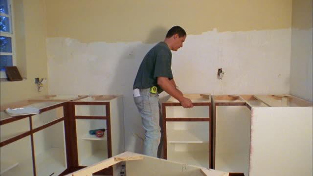 Medium shot pan man installing cabinets in kitchen