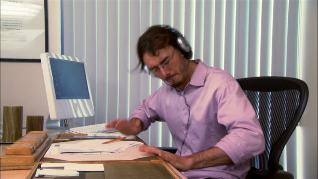 medium shot pan man listening to headphones and banging hands on desk in office - one mid adult man only stock videos & royalty-free footage