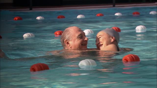Medium shot pan man walking around in swimming pool while holding woman