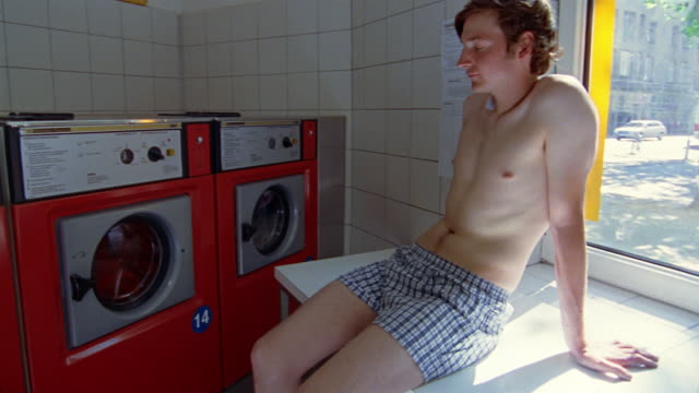 medium shot pan man wearing boxer shorts sitting in laundromat / berlin, germany - 下着点の映像素材/bロール