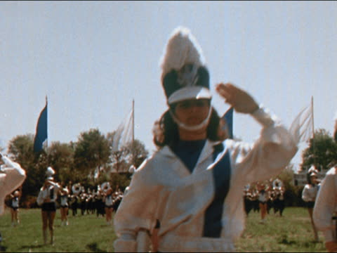1970 medium shot pan marching band with majorettes, flag bearers and rifle bearers in formation on football field - marching band stock videos and b-roll footage