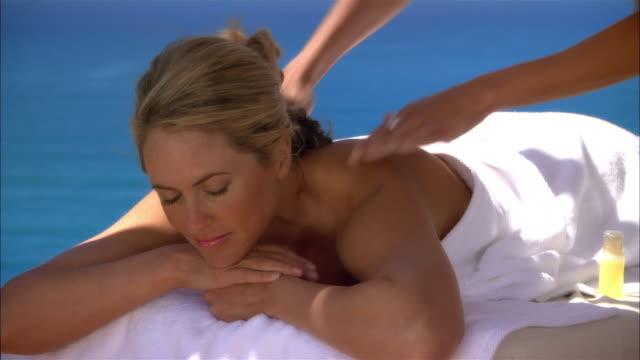 medium shot pan masseuse massaging woman at spa/ monterey county, california, usa - massagetisch stock-videos und b-roll-filmmaterial