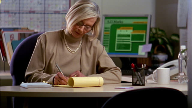 Medium shot pan mature female executive looking up from legal pad at desk / smiling