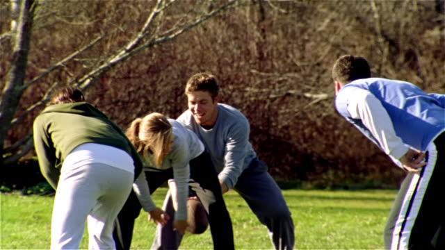 Medium shot pan men and women playing football/ Maine